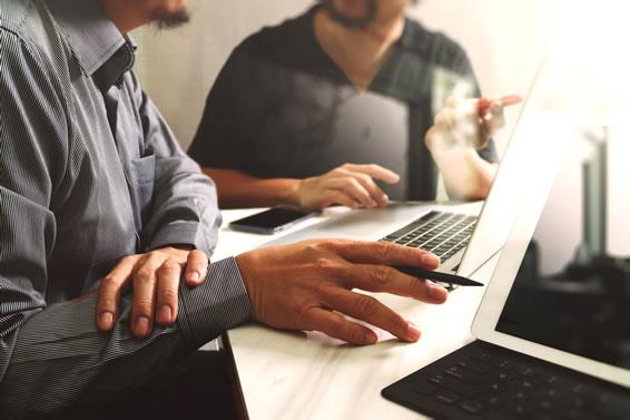 two men working on laptopl